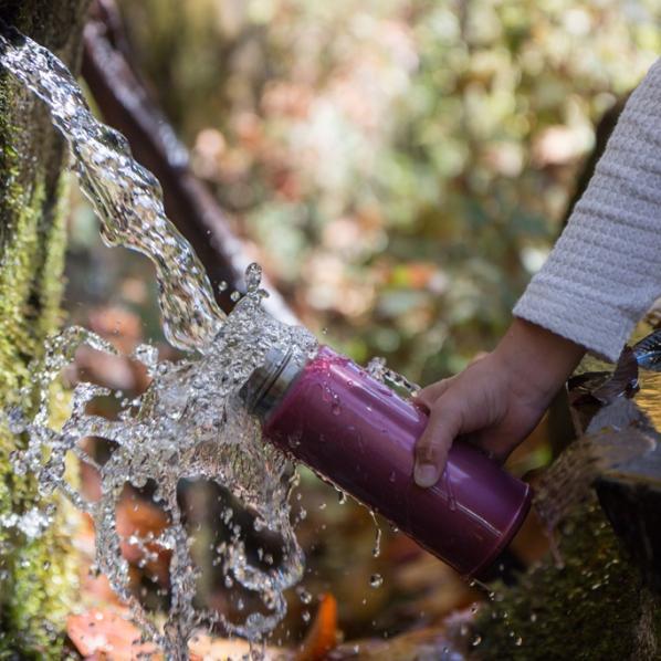 Enfant remplissant sa gourde d'eau à la fontaine