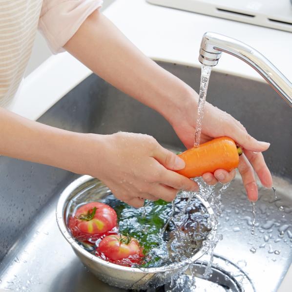 Personne lavant ses légumes sous l'eau, dans un évier.